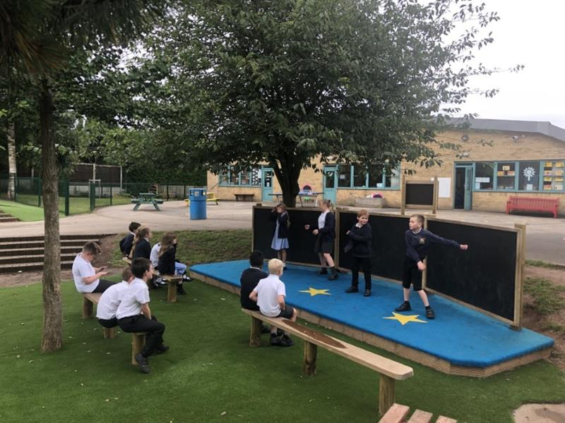 4 children performing on a performance stage with blue safeturf surfacing with yellow stars on, and chalkboard at the back, whilst 9 children sit on benches in the audience. The performance stage and benches have been installed next to two large trees.