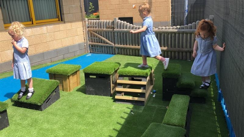 3 girls wearing light blue school summer dresses are playing on get, set go! blocks that have been placed onto artificial grass next to the school building.