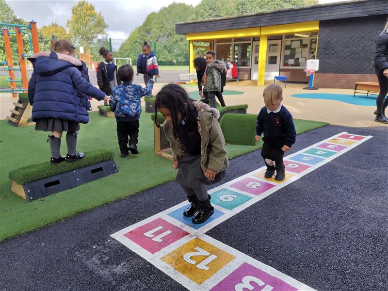 Children playing on a number square created by playground marking
