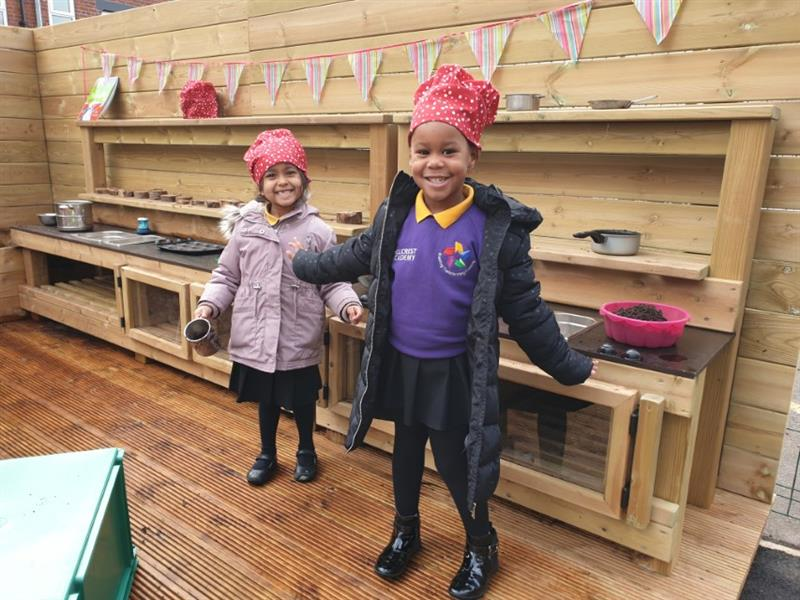 Children standing in front of a playground mud kitchen smiling