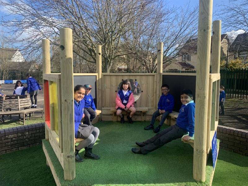 Children sitting in a playground den
