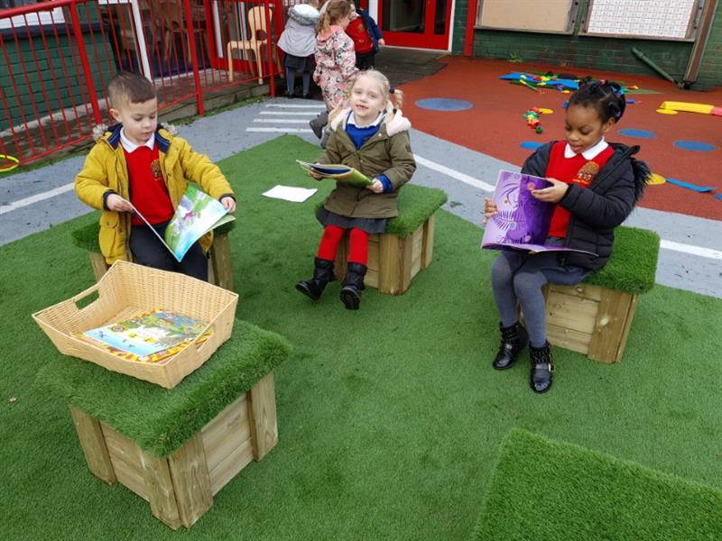 Children reading stories on school playground seating