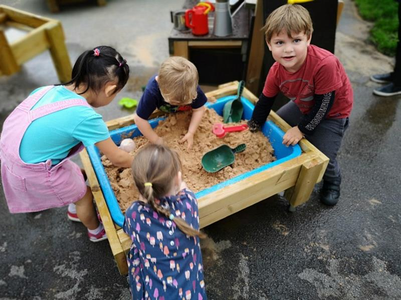 4 children playing with a sand box with one boy wearing a red top with black sleeves is smiling at the camera whilst he plays with the sand.