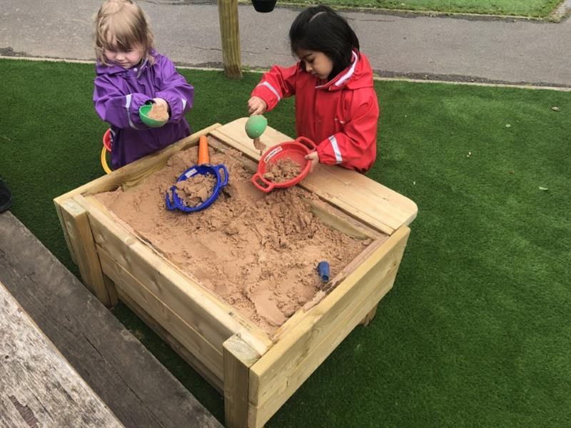 2 girls, one wearing a purple coat and one wearing a red coat are playing with sand in a sandbox. The sandbox has been installed onto artificial grass next to a school path.