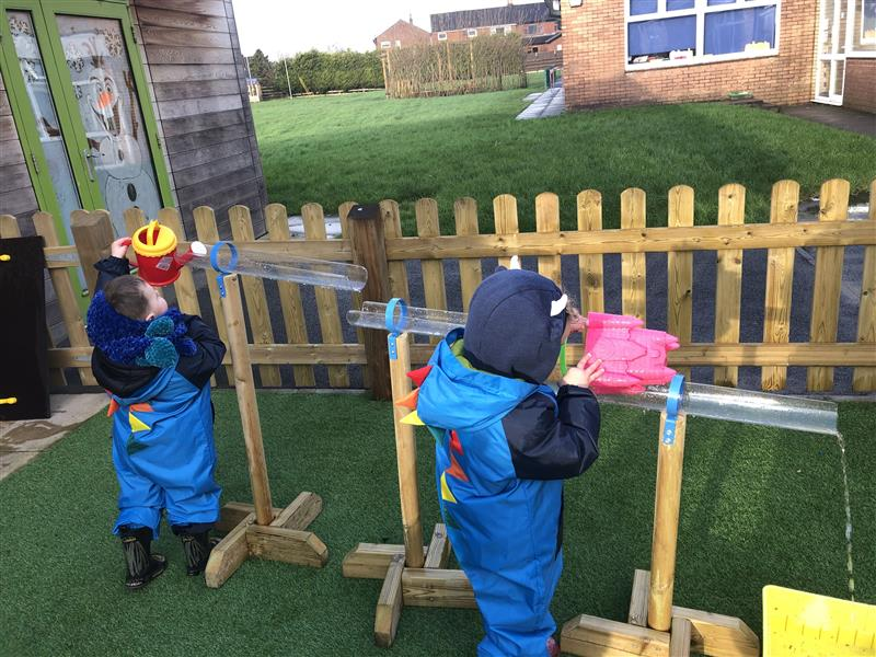 Two children wearing blue waterproof suits and wellies using a watering can and sandcastle bucket to pour water down two water channel stands.