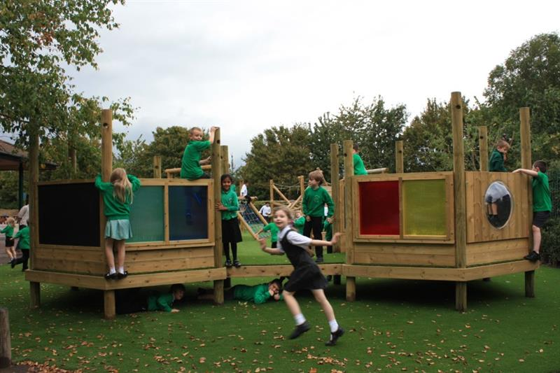 Children playing on themed playground equipment in the playground