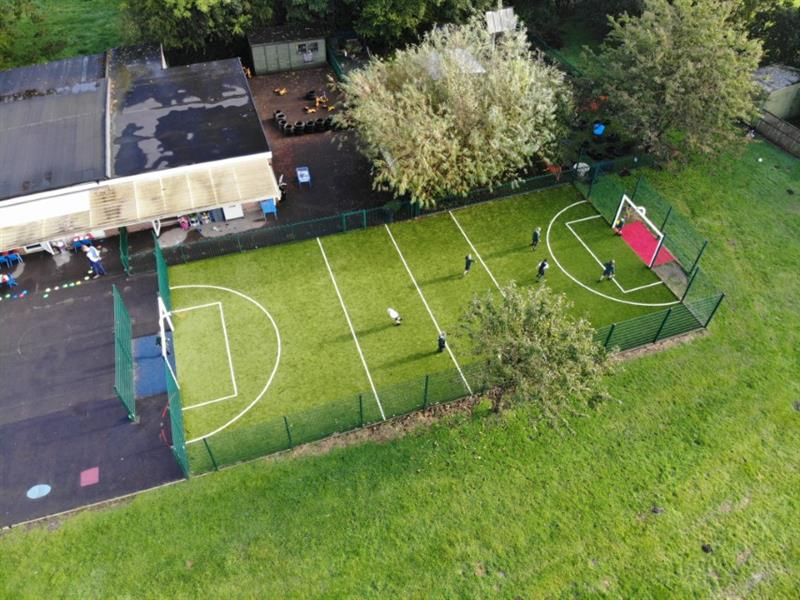 An aerial view of a multi-use games area which has been installed onto a school field with 2 large trees next to it. The muga is also next to the school building.