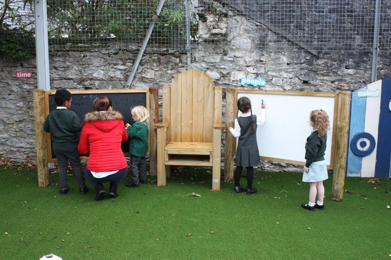 2 children stood at a chalkboard and 2 children stood at a whiteboard with one teacher in a red coat supervising. There is a storytelling chair in the middle of the chalkboard and whiteboard which have been installed onto artificial grass.