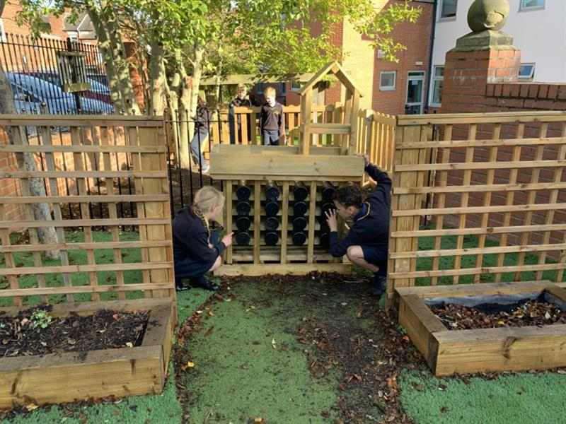 Two children investigating what has moved into their bug hotel