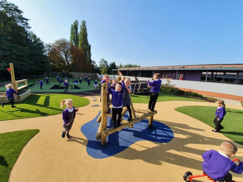 5 children wearing purple jumpers are playing on a small climbing frame which has been installed onto wetpour surfacing whilst other children run around the playground and one child is riding a red trike.