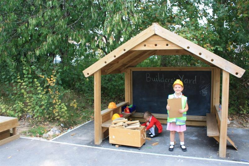 two girls stood inside of a giant playhouse with a chalkboard, one girl wearing a red summer dress, hi-vis jacket and yellow builders hat holding a small clipboard whilst one girl wearing a red cardigan behind a box of blocks.