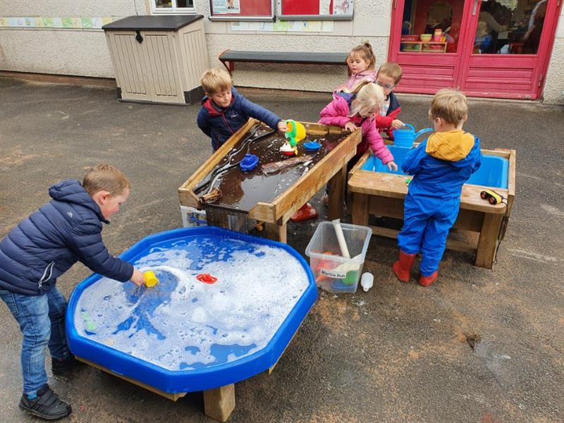 6 children experimenting with water flow on a pentagon play damming station