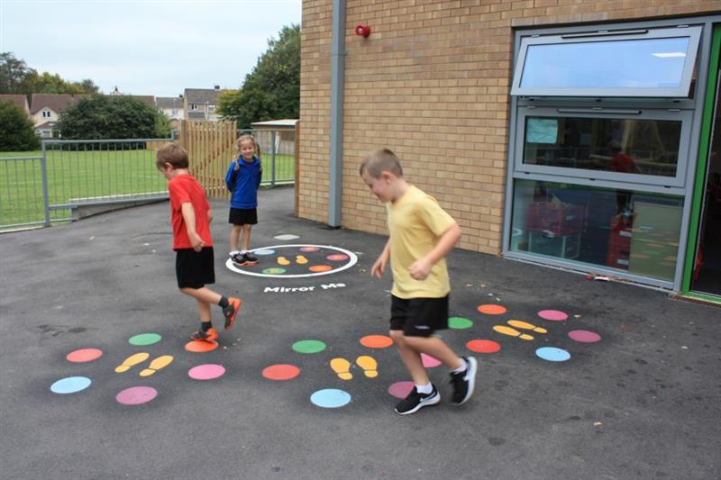 3 children, one wearing a yellow top, one wearing a red top and one wearing a blue top, skipping on multi-coloured playground markings in front of the school building.