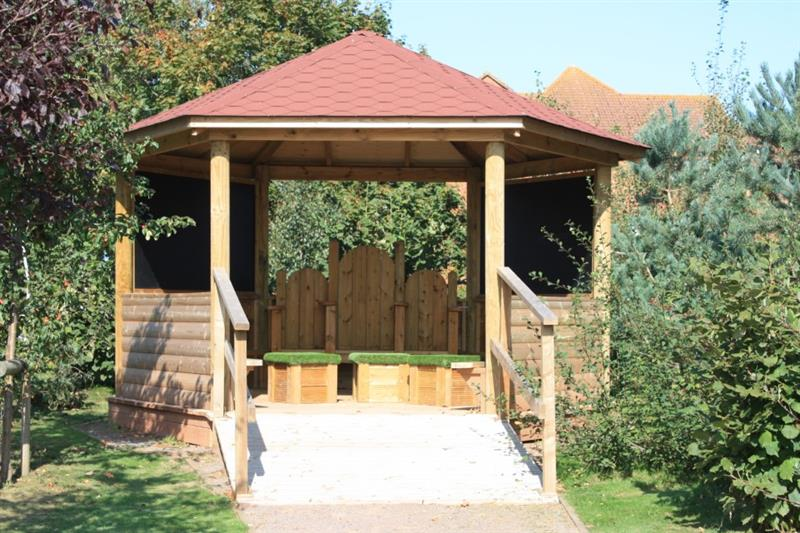 A hexagonal gazebo with a ramp leading up to it for wheelchair access with 3 storytelling chairs and 3 moveable artificial grass topped seats inside.