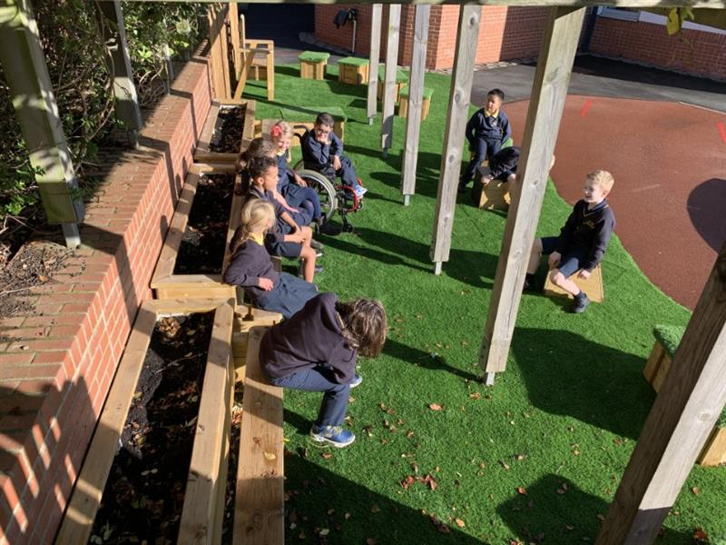 Children sitting on playground seating installed onto artificial grass