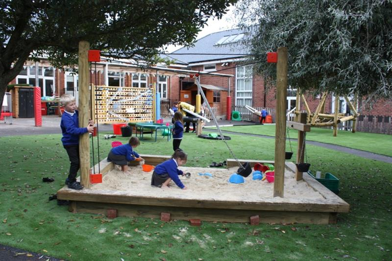 One child is playing with a rope and pulley in a sand area whilst two other children are playing with the sand and making sandcastles. The sand area has been installed onto artificial grass in between two trees and in front of the school building.
