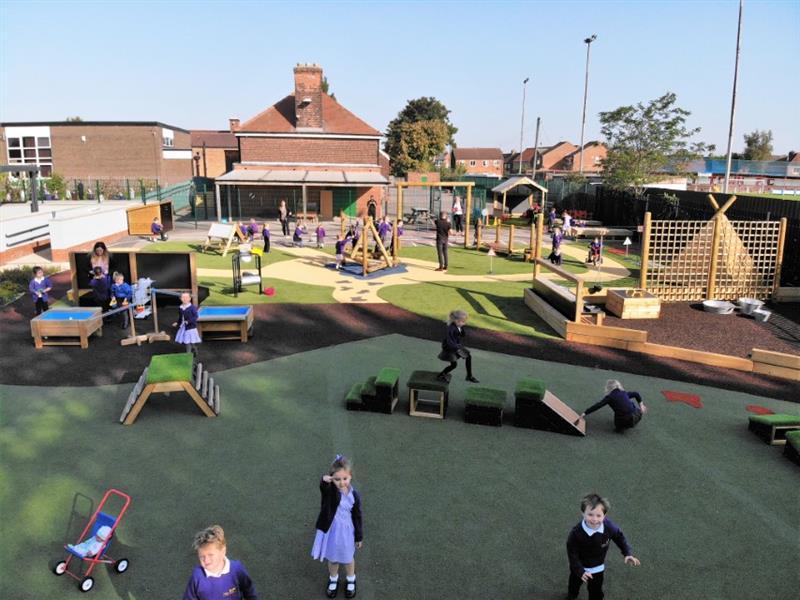 Children running around a huge eyfs playground