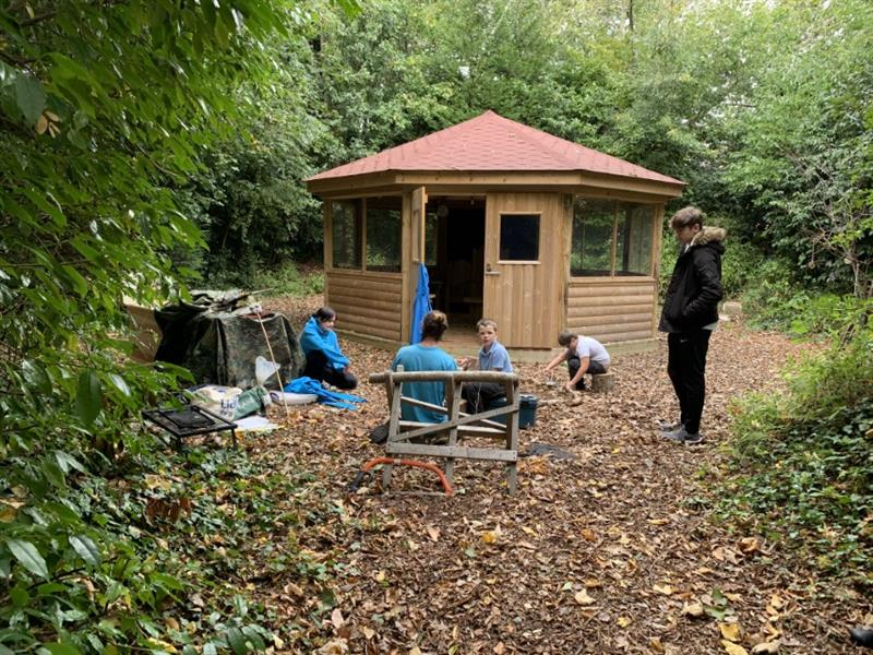 Children participating in forest school lessons next to a gazebo