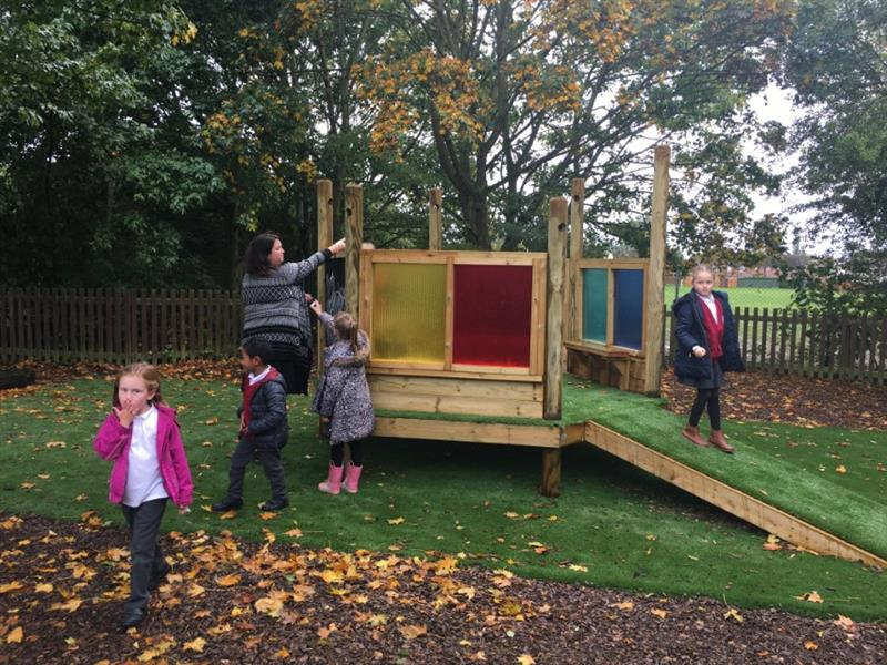 one child walking down the slop from the imagination station whilst 3 children walk away from the imagination station. There is one teacher talking to the children and pointing at a tree. The imagination station has been installed onto artificial grass.