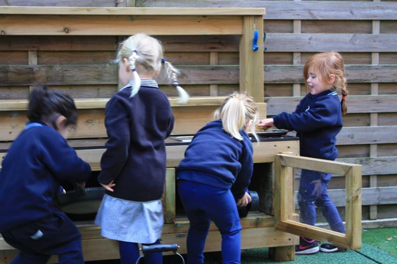 Children playing with a playground mud kitchen