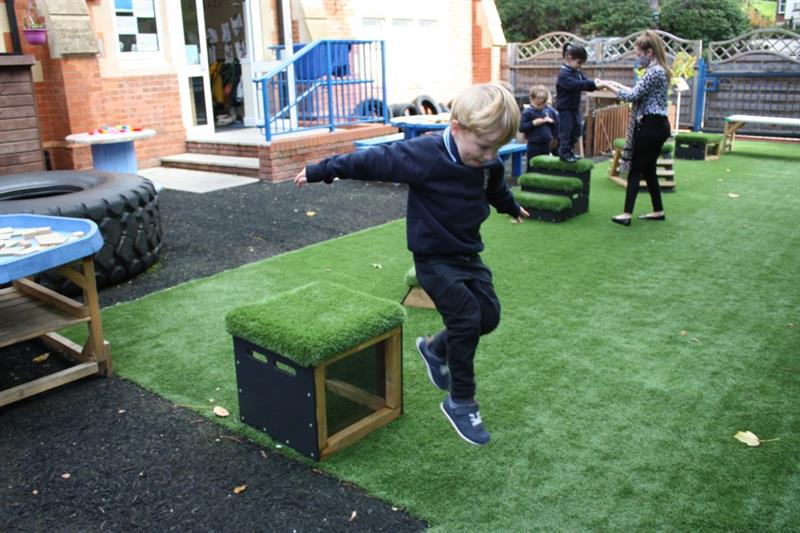 close up photo of a boy with blonde hair jumping off a get, set go! block! which has been placed onto artificial grass whilst 2 more children play in the background assisted by one teacher.