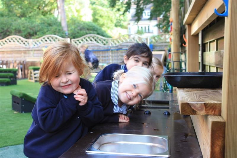 4 children smiling at the camera stood at a mud kitchen whilst one boy plays on get, set, go blocks in the background.