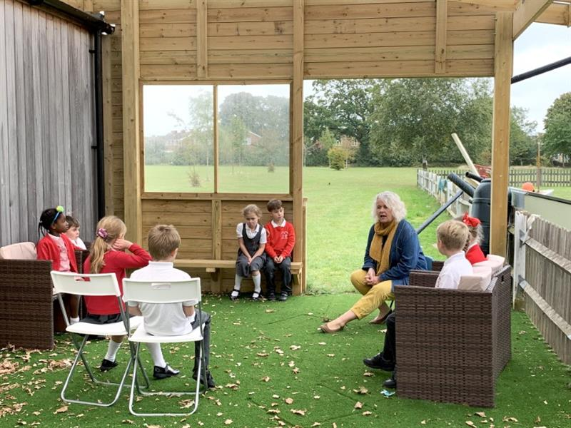 Children sitting under a school playground timber canopy talking to a teacher