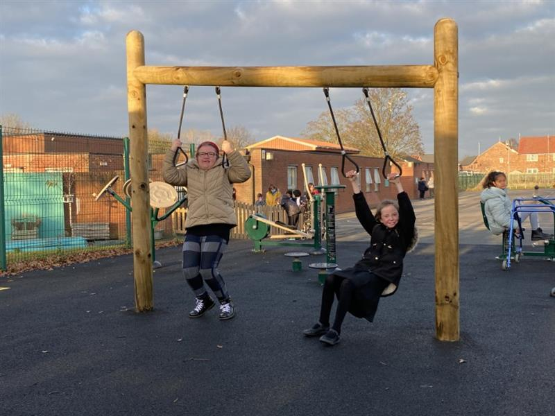 Two children swinging from a heavy work swing on their school playground