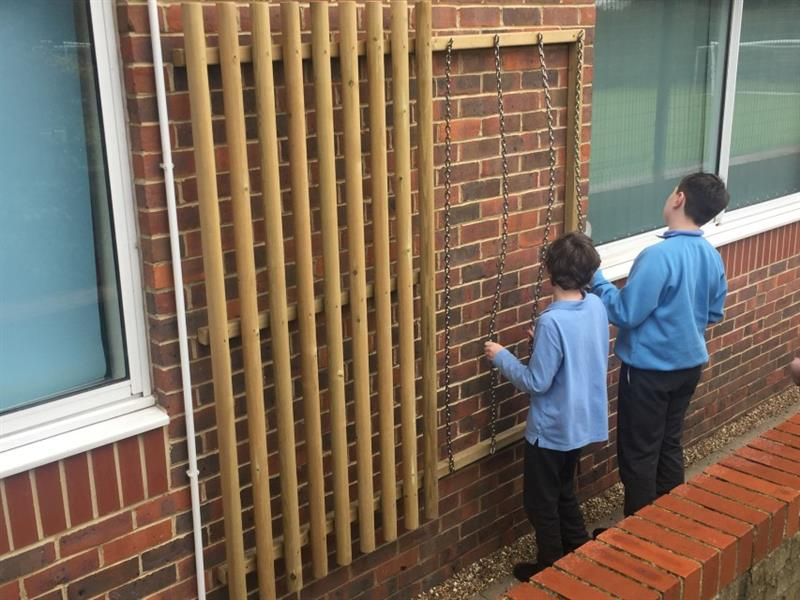 Two boys with brown hair wearing blue jumpers are stood playing with a large sensory panel with dowels and chains that has been installed onto the school building wall in the middle of two windows.
