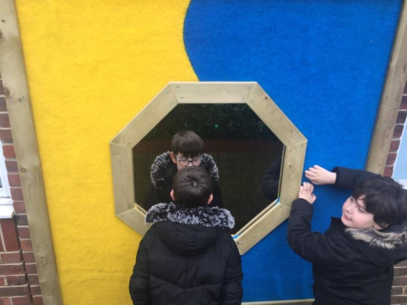 2 children both boys stood in front of a large sensory panel with yellow and blue safe turf and a mirror which is attached to the school wall, both children wearing black coats.