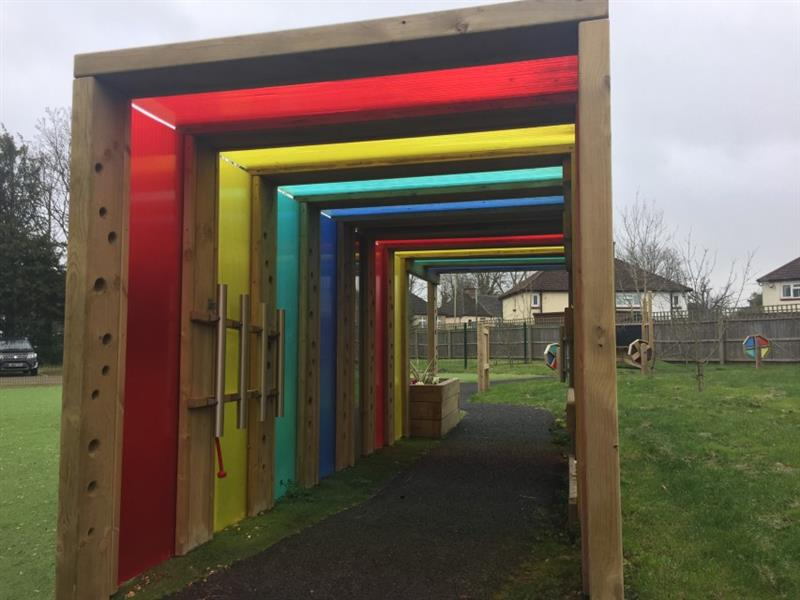 A photo of the inside of pentagon plays sensory tunnel that is made up of timber, multi coloured polycarbonate panels, musical play equipment and planters