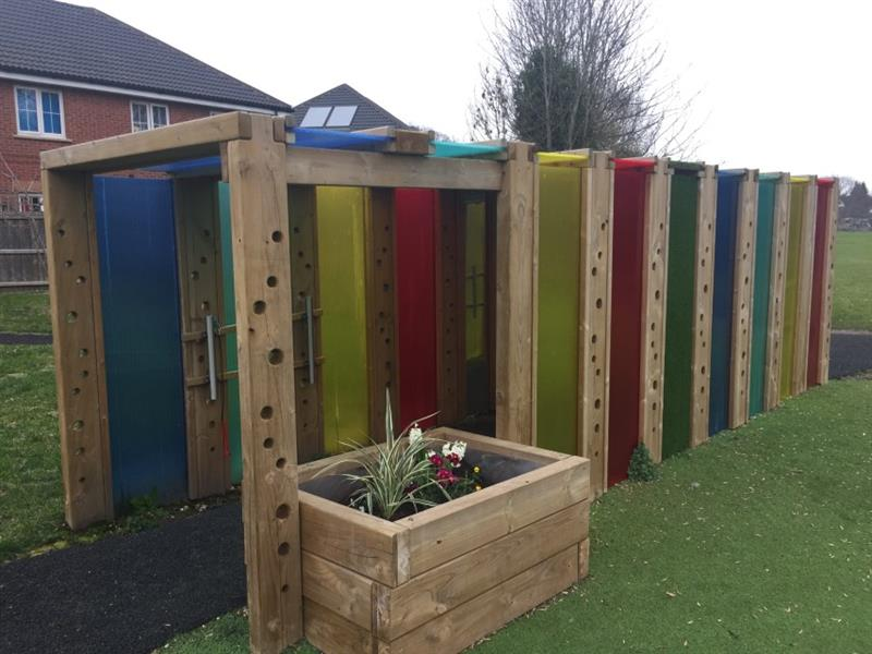 A photo of pentagon plays sensory tunnel that is made up of timber, multi coloured polycarbonate panels, musical play equipment and planters