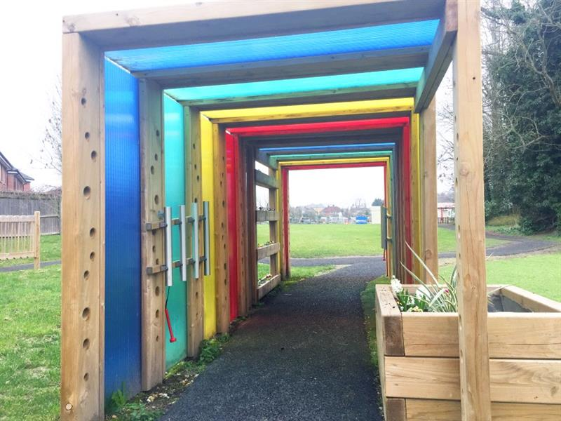 A sensory tunnel with blue, green, yellow and red panels has been installed onto a school field with a footpath going through it. There is a planter with some plants growing at the end of the tunnel.