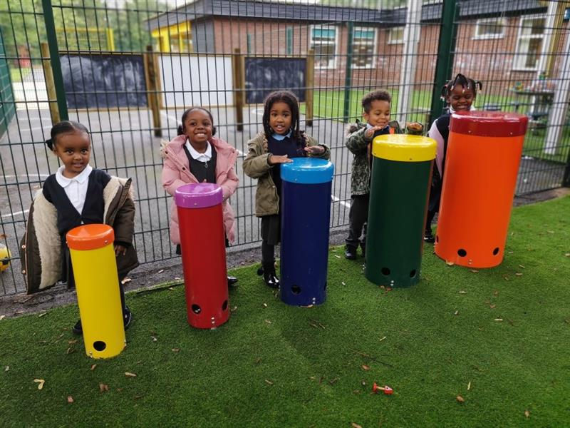 5 children banging on African drums, each child has their own drum which has been installed onto artificial grass.