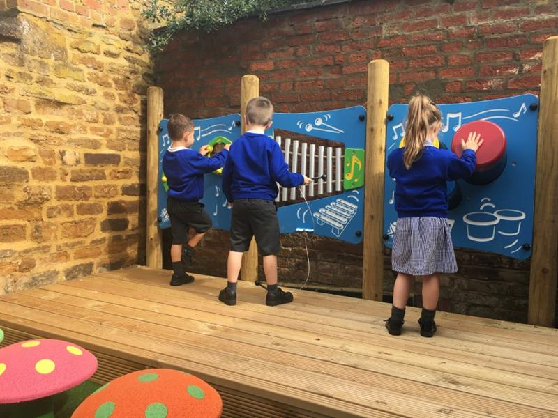 3 children playing on a shaker panel post, a glockenspiel post and a bongo panel post in front of pink and orange mushroom seats.