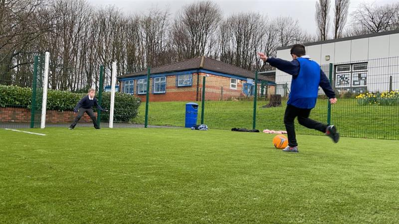 2 boys, one wearing a blue bib and one stood in the goal on a multi-use games area playing football with an orange football. The muga has been installed in front of the school building.