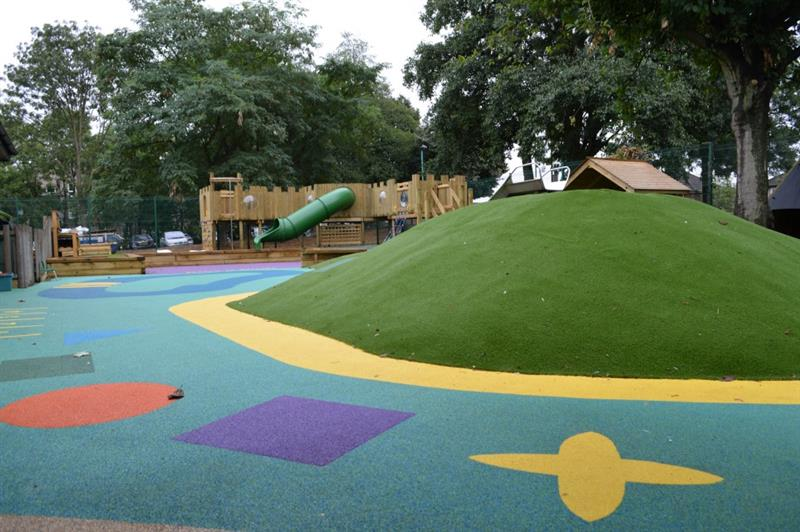 Blue playground surfacing with red, purple, yellow and green shapes on with a green mound covered in artificial grass in the middle. There is a large castle play frame in the background with a huge green slide.