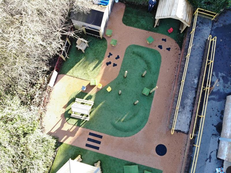 Aerial view of school playground which includes playground surfacing with a zebra crossing, artificial grass with 2 surfacing mounds and a giant playhouse.