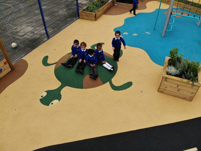 4 children wearing blue school jumpers sat on a turtle feature surface mound smiling at the camera whilst one boy stands on the edge of the mound near a square planter.