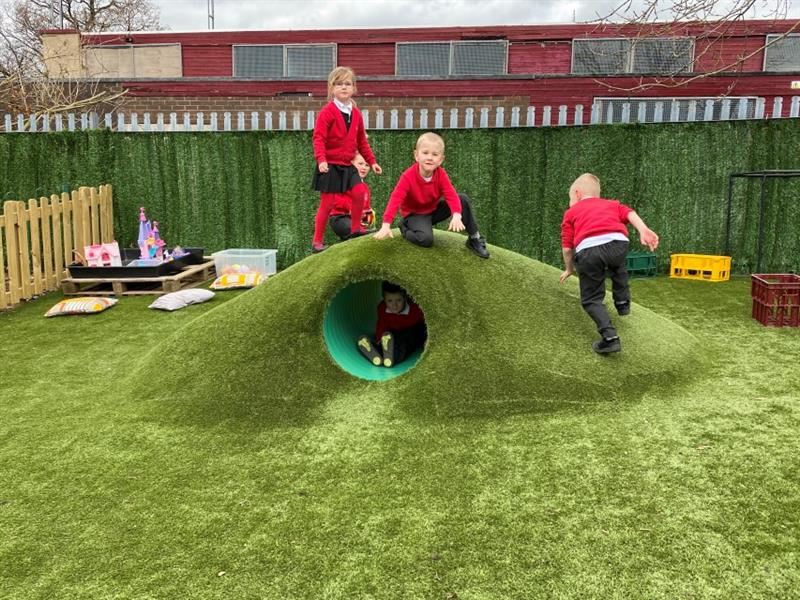 4 children playing on top of a climb through tunnel that has been topped with artificial grass that has been installed in front of the school building whilst one child sits inside of the tunnel.