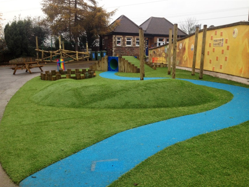 Playground surface mound placed in the middle of school playground which is surrounded by a blue path with a climb through tunnel in the background.