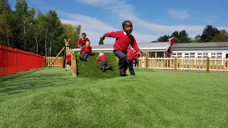 3 children wearing red jumpers, playing on a climb through tunnel whilst one boy runs towards a playground surface mound, the area is covered with artificial grass and is in front of the school building.