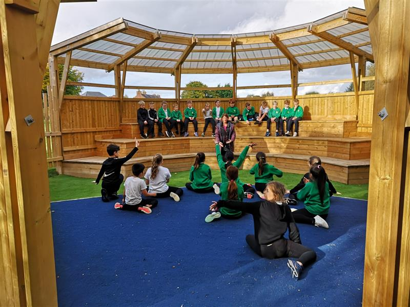 children performing on a playground performance stage with blue saferturf surfacing, benches and a roof