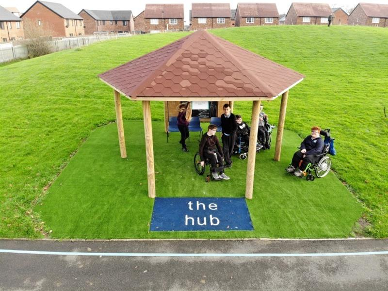 3 pupils are sat in wheelchairs underneath a hexagonal gazebo which has been placed on a school field, next to the school playground. The gazebo has been installed onto the artificial grass with a blue sign saying the hub made with safeturf surfacing.