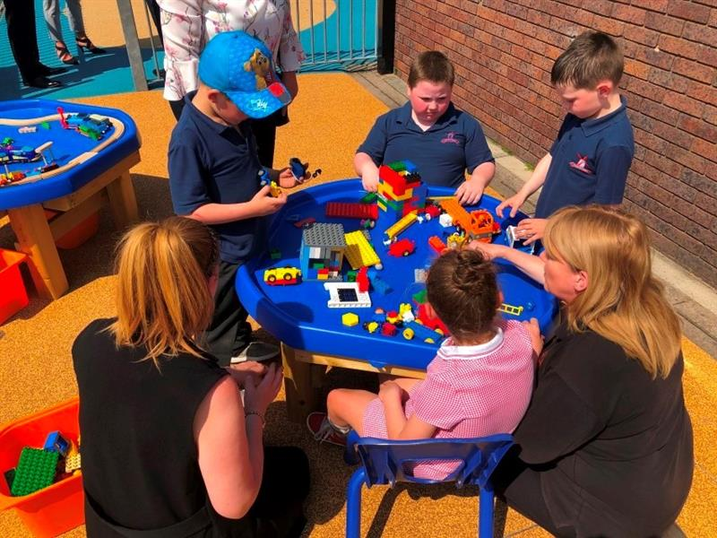 4 children, 3 boys wearing navy blue school tops and one girl wearing a red summer dress are playing with lego and cars at a tuff spot table. The table has been placed next to another tuff spot table next to the school building. There are 3 teachers supervising.