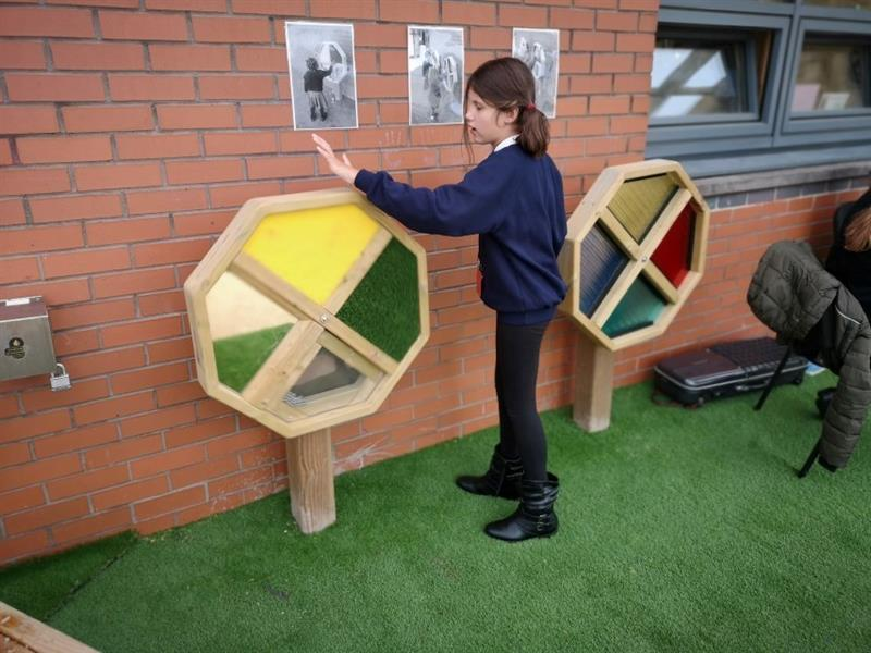 One girl with brown hair playing with the sensory spinners that have been installed onto artificial grass in front of the school building. There are 3 photographs stuck onto the school building wall to show children how to play with the sensory spinners.