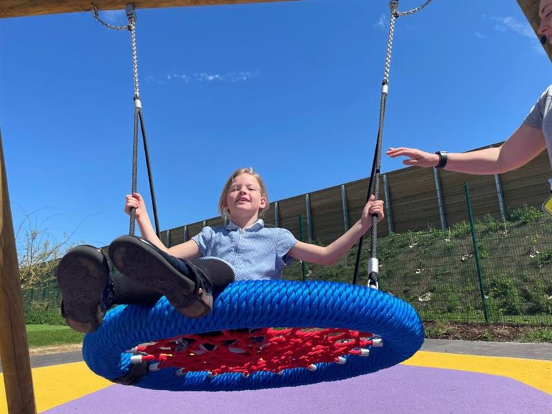 One girl with blonde hair wearing a blue summer dress is sat on a circle swing whilst one teacher stands at the side of the swing pushing her. The swing has been installed onto yellow and purple playground surfacing.