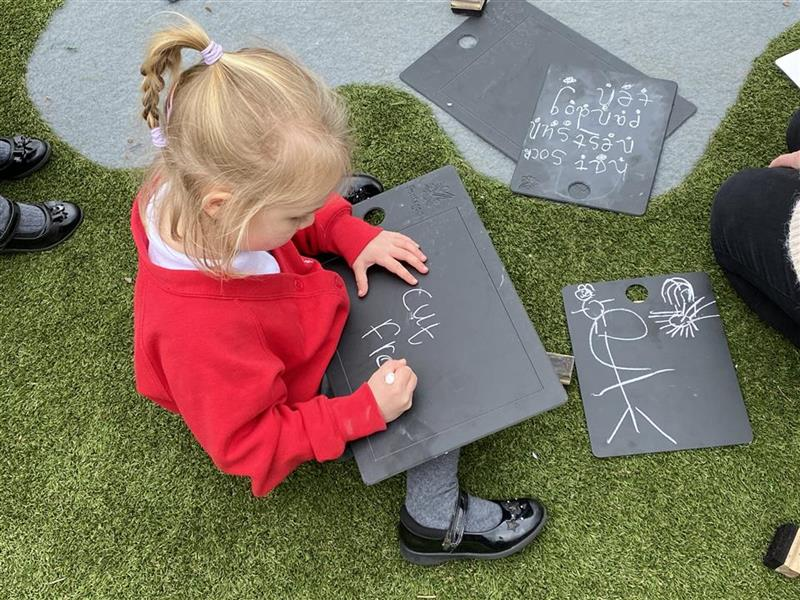 A girl drawing on our scribble boards.
