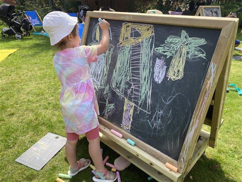 a  young girl playing on the easel on wheels