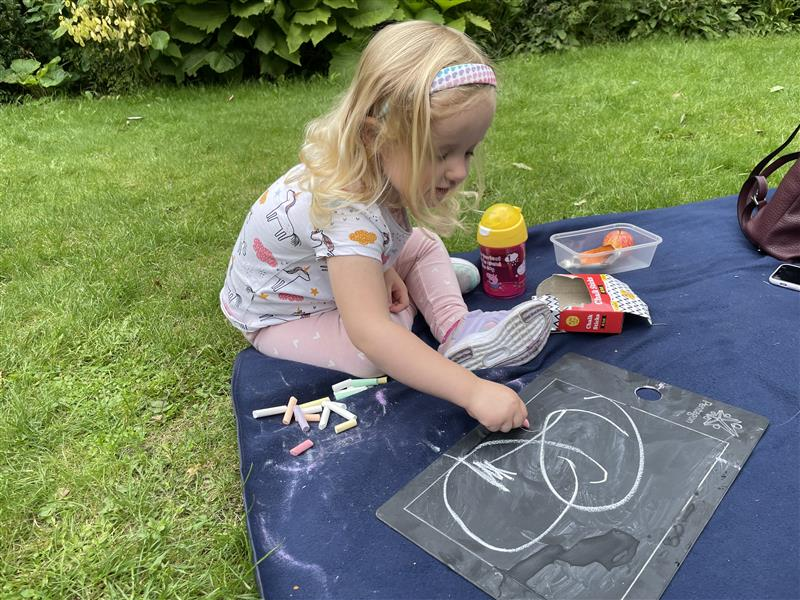 a young girl using our scribble board